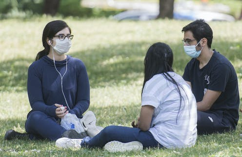 Young people sitting in a park wearing masks as they chat.