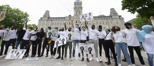 Youth stand in a line singing at a demonstration to denounce racism and police violence, June 7, 2020 in front of the legislature in Québec City.