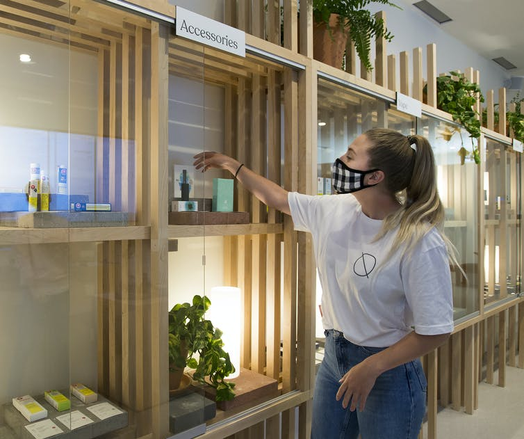 A woman reaches into a display cabinet at a cannabis store