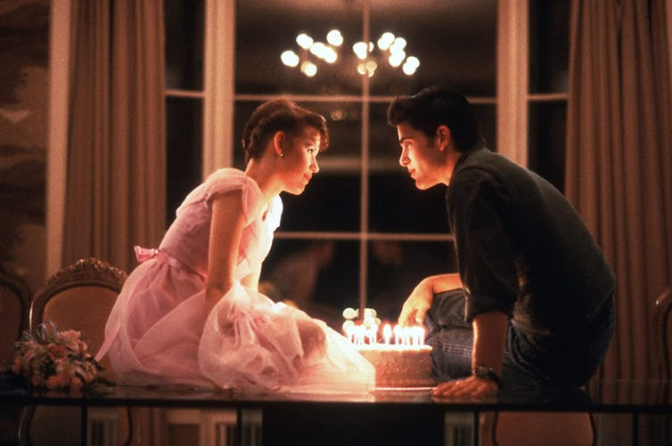 A man and a woman sitting on a table with a birthday cake filled with candles in between them