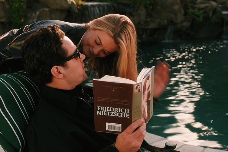 An image of a man sitting down reading a book and a woman leaning over his shoulder to look into his face