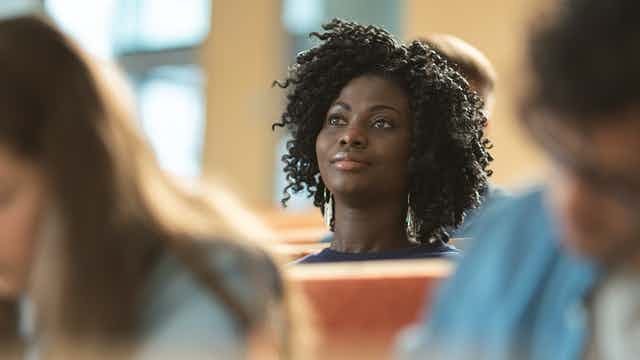 A black woman student focuses her attention in class.