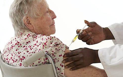 An older woman receives an injection in her upper arm from a health-care worker
