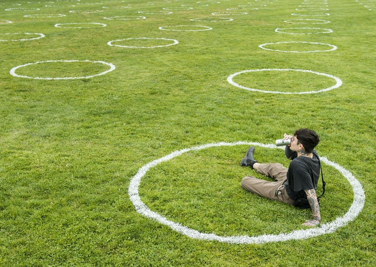 A man sits in a white circle painted on the grass at a park and drinks a beer