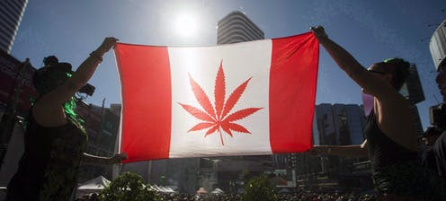 People at a gathering hoist a Canadian flag with a marijuana leaf instead of a maple leaf in the centre.