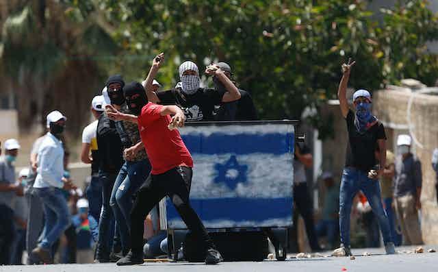 Palestinian protesters throw rocks at Israeli troops