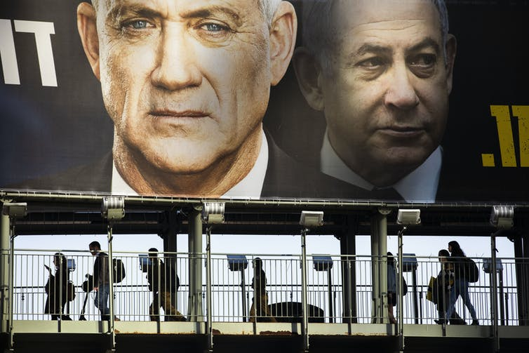People walk past an election sign showing Netanyahu and Gantz