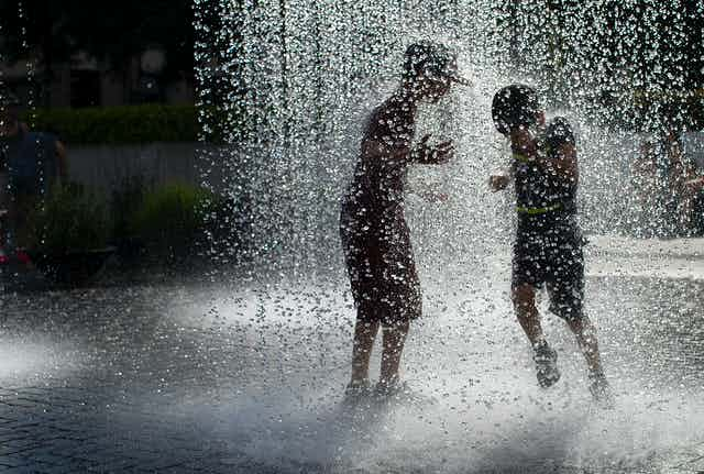 Two boys cool off in a fountain