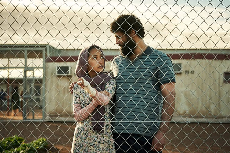 A film still, set in an immigration detention centre, a woman and a man stand behind a fence.