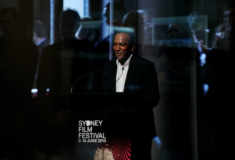 A man wears a suit and stands behind a lectern reading 'Sydney Film Festival'