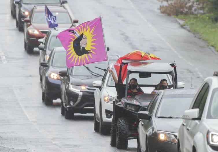 A convoy of vehicles with First Nations flags drive along a road