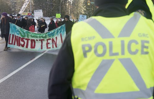Protesters walk along a road carrying signs as a police officer looks on
