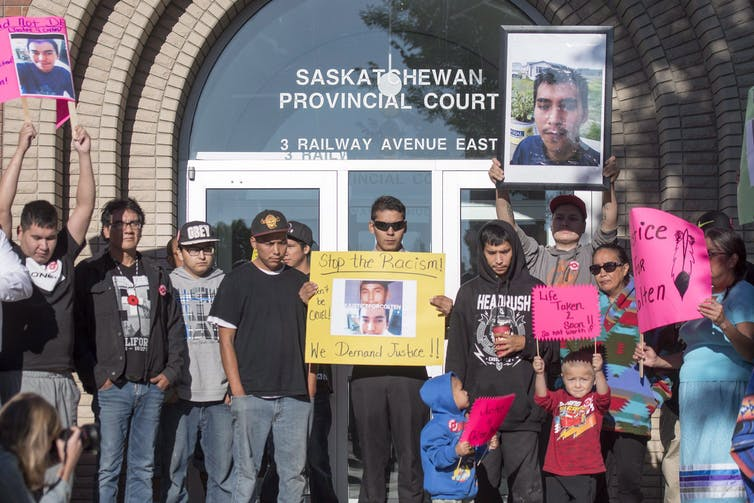 A group of people carrying signs and pictures of Colten Boushie in front of the courthouse.