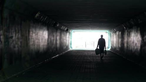 Person walking alone in dark city tunnel