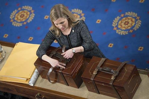 A woman unbuckles a strap around a box.