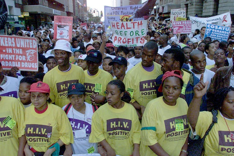 Protesters wearing yellow 'HIV Positive' shirts hold signs and banners