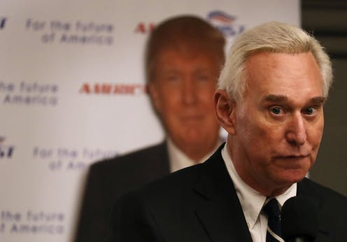 Roger Stone in front of a poster showing an image of Donald Trump.