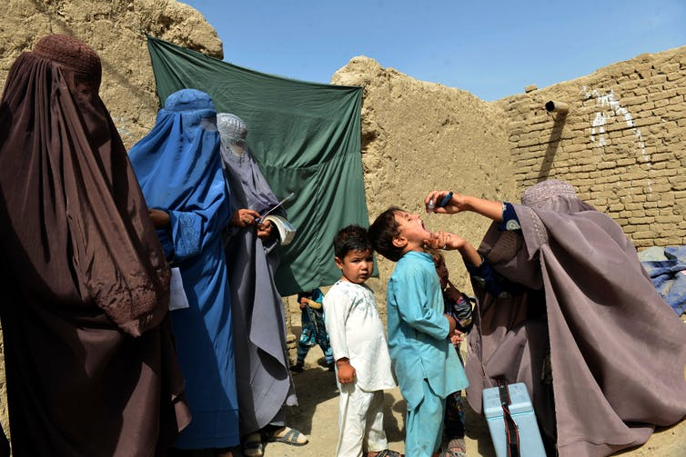 Afghan women in burqas vaccinate young boys