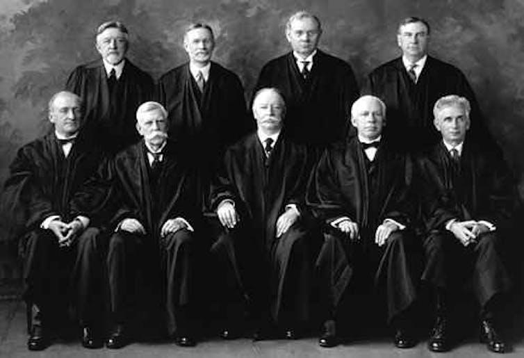 Nine men in black judges' robes.