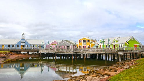 A blue, pink, yellow and green houses on a wooden pier over a small bay. The bay is lined with red rocks on top of which sit a green lawn. The sky behind the houses is filled with white clouds.