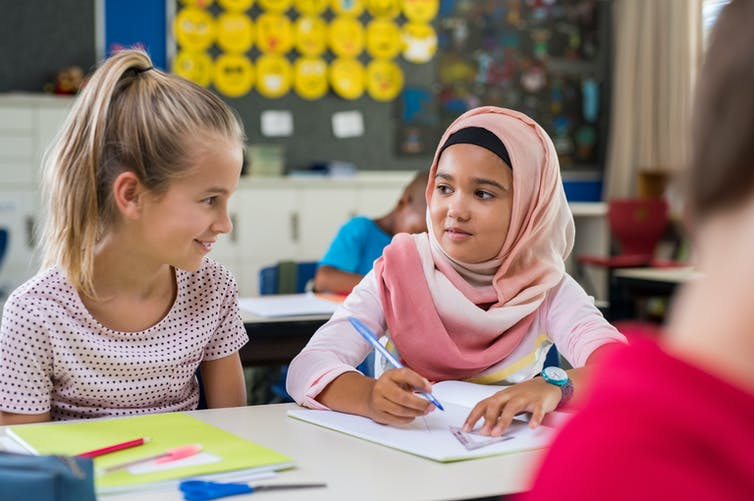 Two female students, one of whom wears a hijab, sit in a classroom talking.