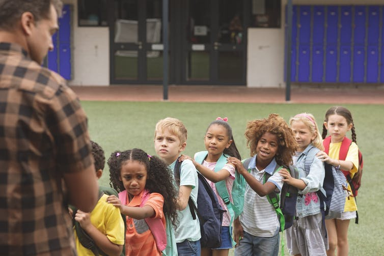 A teacher stands outdoors and faces a line of schoolchildren of diverse racialized backgrounds.