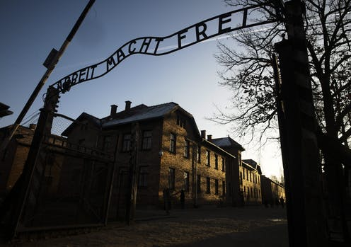 The sun lights the buildings behind the entrance of the former Nazi death camp of Auschwitz-Birkenau in Oswiecim, Germany
