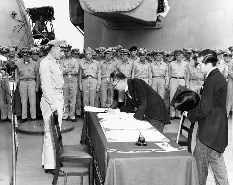 Japanese foreign affairs minister Mamoru Shigemitsu signs the Japanese Instrument of Surrender aboard the USS Missouri as General Richard K. Sutherland watches
