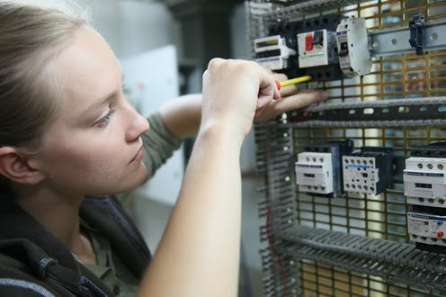 Young woman learning to set up electrical circuit.