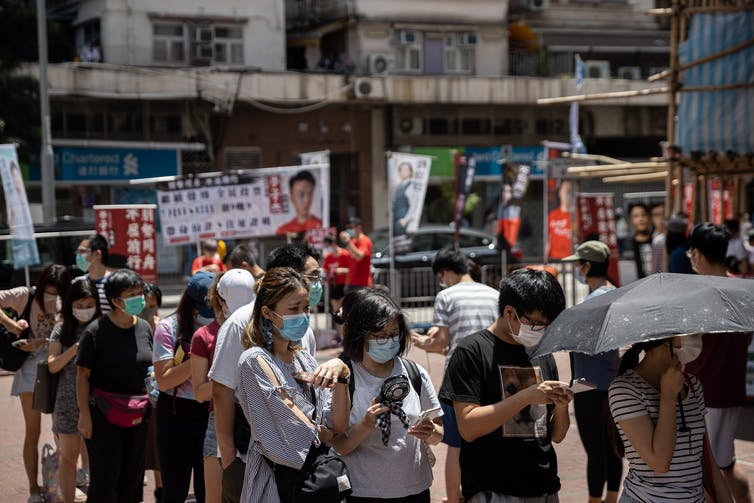A queue of people on a Hong Kong street wearing face masks.