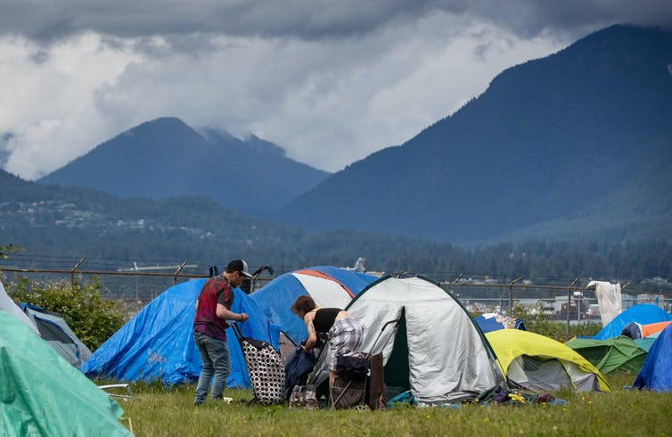 People at a homeless tent encampment in Vancouver with mountains in the background.