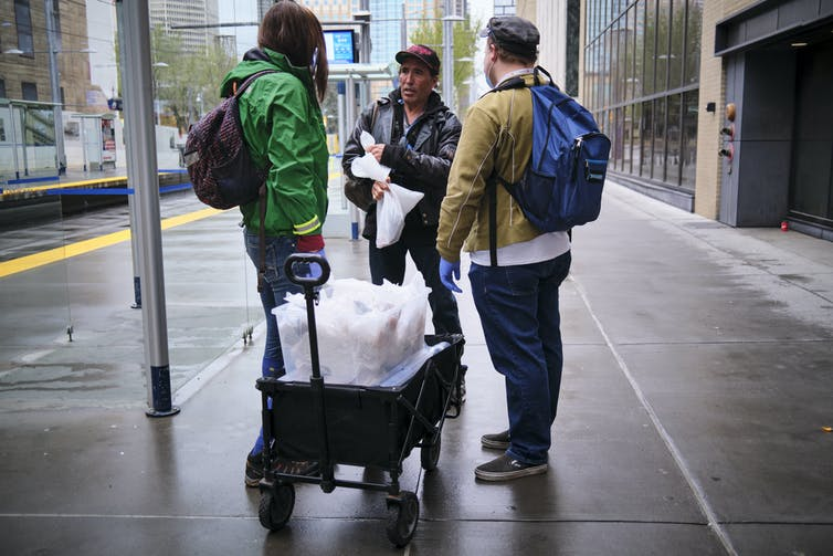 Volunteers chat with a homeless man on a street in Calgary.