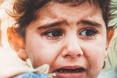 A young girl weeps.