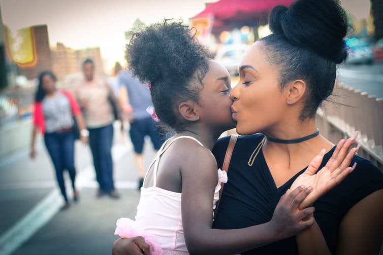 A mother kisses her young daughter in a public setting, with people in the background walking behind them.