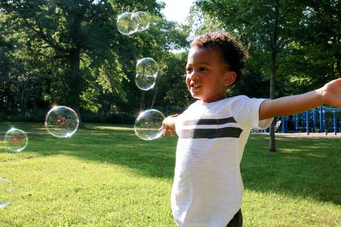 A Black child stands in grass with a playground behind him with his arms open as bubbles float around him.