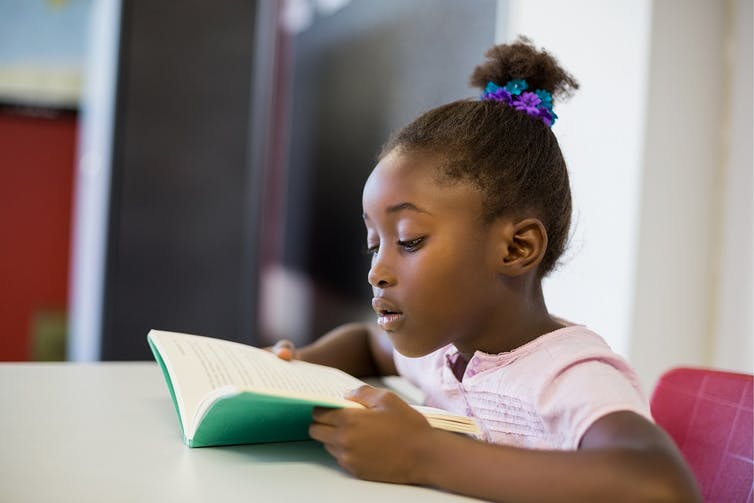 A girl who is Black is reading a book at a school desk.