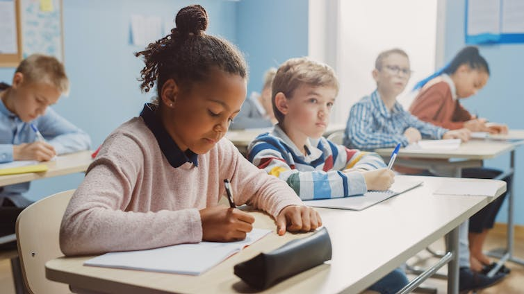 A classroom of students who are middle-school aged are writing a test.