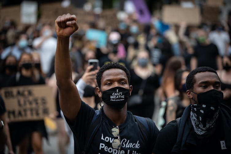 A young Black man raises his arm during a Black Lives Matter protest