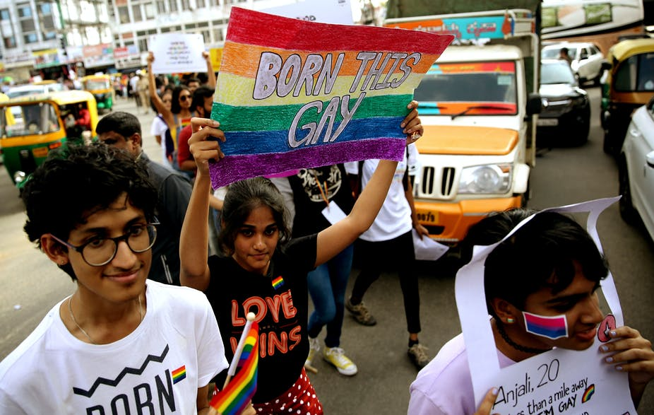 Woman in India holding sign that says born is gay