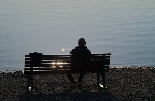 Image of a man sitting alone on a bench.
