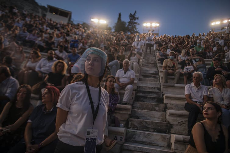 An usherette wears a face shield as she stands in front of rows of audience members in twilight at the Odeon of Herodes Atticus in Athens, Greece.