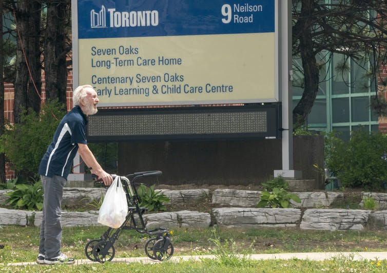 A smiling, bearded man toting a plastic bag and using a walker takes a walk outside a long-term care home in Toronto, with a sign with the name of the home — Seven Oaks — in the background.