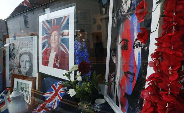 Photos of Vera Lynn as a young and older woman are seen in a window, with the Union Jack flag, a teapot and flowers,  as her funeral procession goes through the village of Ditchling, southern England, July 10, 2020.