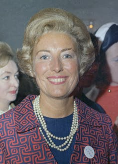 Vera Lynn stands smiling wearing a triple string of pearls and a jacquard blue and orange jacket in 1969.