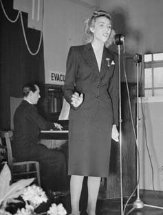 Vera Lynn stands at a microphone singing, backed by a pianist.