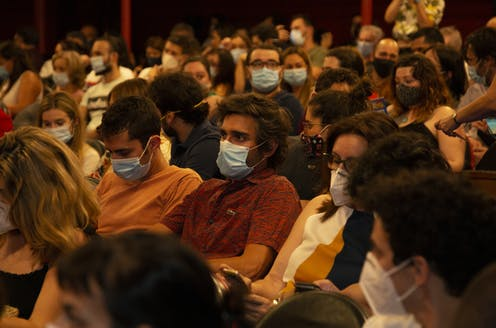 Seated crowd of people wearing masks