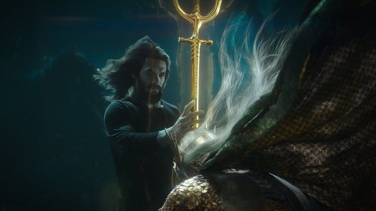Aquaman holds a gold staff.