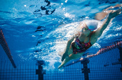 A women in goggles and a cap swimming lengths in a pool