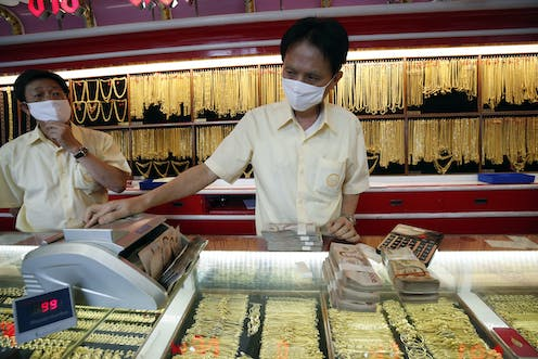 Shopkeepers in a jewellery shop wearing masks.