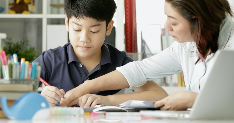 A mother is helping her teenage son do homework